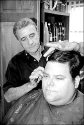 CHRIS KELLY  Ron Kroeschel, who works in Shrewsbury, gets a trim from Salvatore Izzo Jr., who has been cutting hair for more than 50 years.