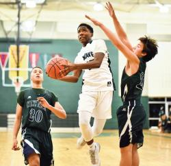 Long Branch High School's Marc Dennis drives to the basket between Colts Neck High School defenders Lloyd Daniels, left, and Brendan Clarke during the Dec. 18 game played in Long Branch. The host Green Wave won the season opener for both teams, 57-54.  STAFF PHOTOGRAPHER ERIC SUCAR