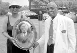 CHRIS GAETANO Thomas Jennings, the great-great-grandson of Thomas Titus, stands with niece Frances Moore holding a picture of the son of Titus, a freed slave whose work was recognized at the June 16 dedication ceremony.