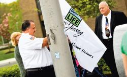 Robert Peters, whose son Christian died unexpectedly in 2007, helps raise the Donate Life flag at JFK Medical Center. Christian's organs were donated to various recipients after his passing.