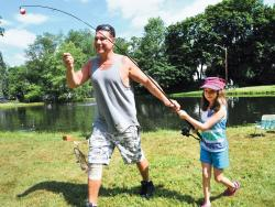Steve Marosi escorts his daughter Olivia, 7, and her catch to the measuring area during the Metuchen Recreation Commission's annual Youth Fishing Derby held at Tommy's Pond on July 21.  SCOTT FRIEDMAN