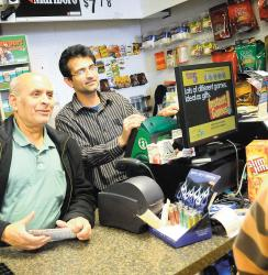 Dhiren Desai (l) and Vikram Chaudhari sell lottery tickets at the Esquire News & Smoke Shop, Freehold, on April 3. Many small-business owners are concerned that privatization of the lottery would have a negative impact on business.  ERIC SUCAR staff