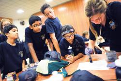 A group of young cadets watch as Alyssa Maurath, far right, dusts for fingerprints during a session of the Edison Junior Police Academy, held at Woodrow Wilson School in Edison on Aug. 6.  STAFF PHOTOGRAPHER ERIC SUCAR