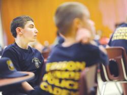 Twelve-year-old Frank Colavolpe, left, along with cadets of varying ages, listens to a presentation on crime scene investigations by Edison police Detective Joe Sudnick during the Edison Junior Police Academy.  STAFF PHOTOGRAPHER ERIC SUCAR