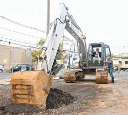 Metuchen Mayor Thomas Vahalla operates a backhoe with guidance from a construction worker during the Oct. 1 groundbreaking at the Pearl Street development site.  PHOTO COURTESY OF WOODMONT PROPERTIES