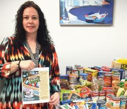 Lisa Marie Stecker of Greater Media Newspapers' Advertising Department shows some of the food that was donated during a holiday food drive sponsored by the newspaper group from Dec. 9-21. The food was brought to the Food Bank of Monmouth and Ocean Counties, Neptune, for distribution throughout the region.  KATHY McBAIN/STAFF