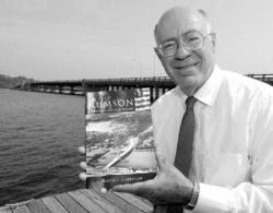 JEFF GRANIT At the Rumson side of the Oceanic Bridge, Randall Gabrielan holds a copy of his recently released book, Rumson: Shaping a Superlative Suburb.