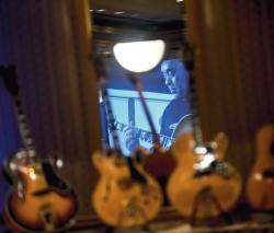 Above: A mirror reflects an image of Christopher Wylde playing a Sam Koontz guitar in a video shown recently at the Pines Manor in Edison. Wylde, of Milltown, hosted the Koontz guitar celebration with 31 hand-crafted guitars owned by the late Howard Krive of Metuchen. Left: A guitar from the collection is exhibited. More photos at gmnews.com.  PHOTOS BY JEFF GRANIT staff