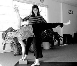 Inner Light yoga studio owner Denise Trimble assists instructor Diane Erbe-Maltabes in a half-moon pose in the Inner Light yoga studio located in Lion's Plaza on Route 130.