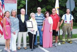 Roosevelt Avenue in North Brunswick is now also known as Lettieri Way in honor of World War II veteran Louis Lettieri. Pictured (l-r) are Lou Ann Benson, director of Parks, Recreation and Community Services; Councilwoman Cathy Nicola; Councilman Bob Davis; Louis's wife Angela; their son, Thomas; Thomas's wife, Colleen; Councilman Carlo Socio; and North Brunswick firefighter Corey Blake.  PHOTO COURTESY OF CRAIG YETSKO