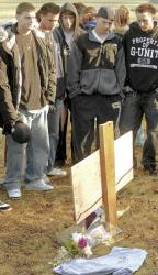 Above, Freehold High School students placed personal items at a roadside memorial where three of their fellow  students were killed in a Jan. 10 collision. At left, friends of the three teenagers came to the Kozloski Road, Freehold Township, site on Jan. 11 and signed a T-shirt for the boys at a roadside memorial.