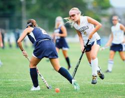 Freehold High School's Jess Pianko, right, pushes the ball up the field, passing Lacey Township High School defender Kristen Santoro during the field hockey season-opener on Sept. 5 in Freehold. The Colonials, the defending Central Jersey champions, will be chasing championships again this fall.