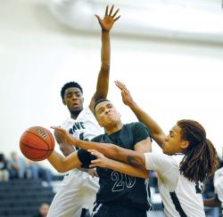 Colts Neck High School's Lloyd Daniels, middle, looks to put up a shot between a pair of Long Branch High School defenders — Ron Anderson, left, and Brandon Yutko — during the season-opening game played in Long Branch Dec. 18. The host Green Wave won, 57-54.  STAFF PHOTOGRAPHER ERIC SUCAR
