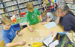 Sherry Prioli watches as her sons Joe, 12, and Nick, 10, play a numbers game at the Howell Public Library. The eight Prioli children have been home schooled.  STAFF PHOTOGRAPHER ERIC SUCAR